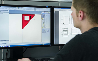 Man looks at CAD drawing of a BINDER chamber displayed on the computer monitor